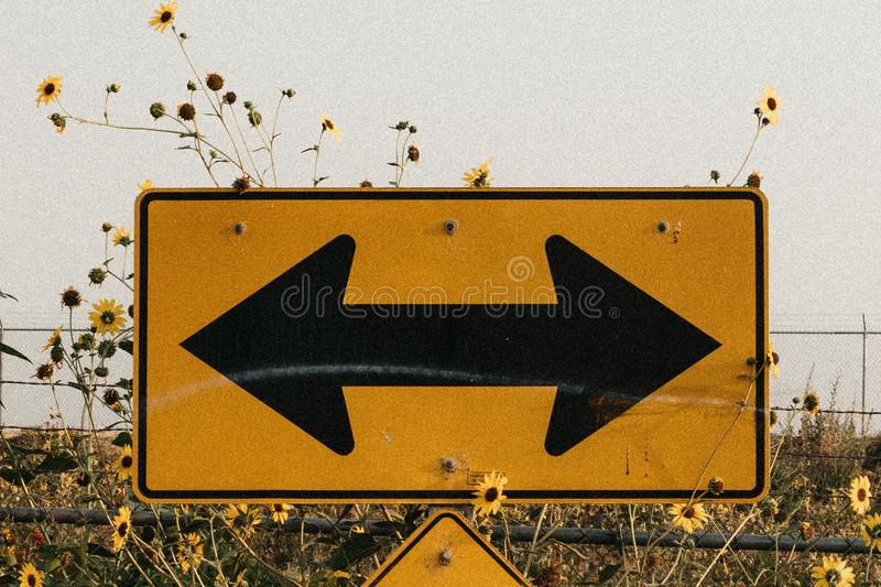 Closeup shot of a yellow road sign in a field with black arrows pointing both ways royalty free stock photography