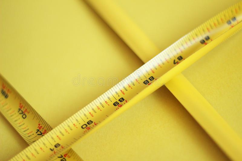 Closeup shot of a yellow stretched measurer or ruler on a yellow background. A closeup shot of a yellow stretched measurer or ruler on a yellow background stock image