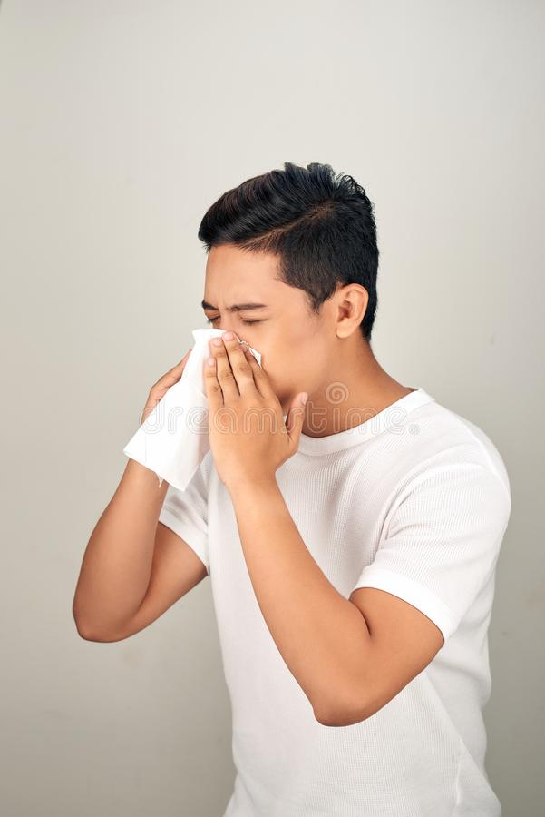 Closeup of sick Asian man blowing nose into tissue, suffering from common cold. Medical and healthcare concept on white background stock images