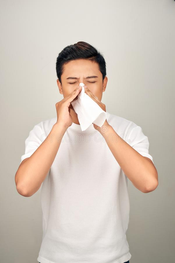 Closeup of sick Asian man blowing nose into tissue, suffering from common cold. Medical and healthcare concept on white background stock image