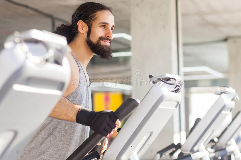 Closeup side view portrait of successful young adult sport man with long curly hair training alone. Handsome male doing exersices royalty free stock images
