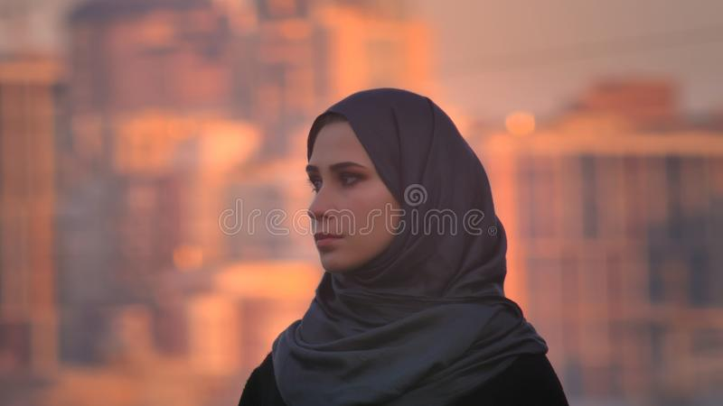 Closeup side view portrait of young attractive female in hijab looking straight at camera with urban city on the stock image