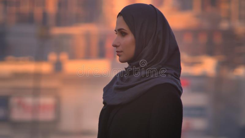 Closeup side view portrait of young attractive female in hijab looking straight at camera with urban city on the stock images