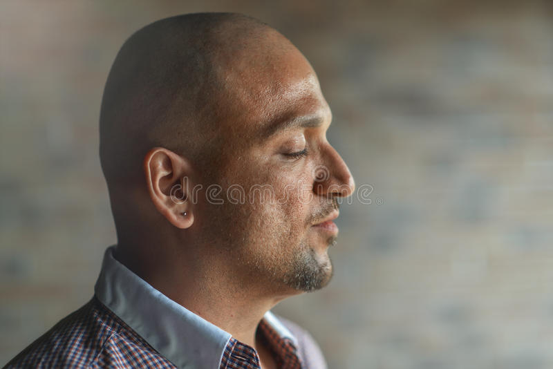 Closeup side view profile portrait of handsome young indian man with his eyes closed, thinking or meditating, royalty free stock photo