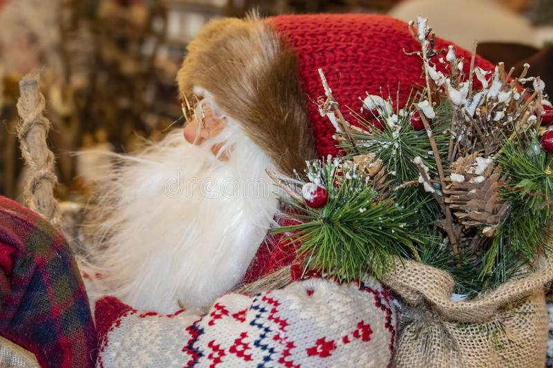 Closeup side view of Santa figure-decoration in ski cap and sweater with burlap bag of Christmas greenery and a walking stick stock photography