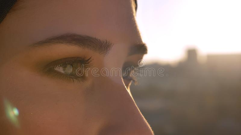 Closeup side view shoot of young attractive female face in hijab with eyes looking forward with urban city on the royalty free stock photo
