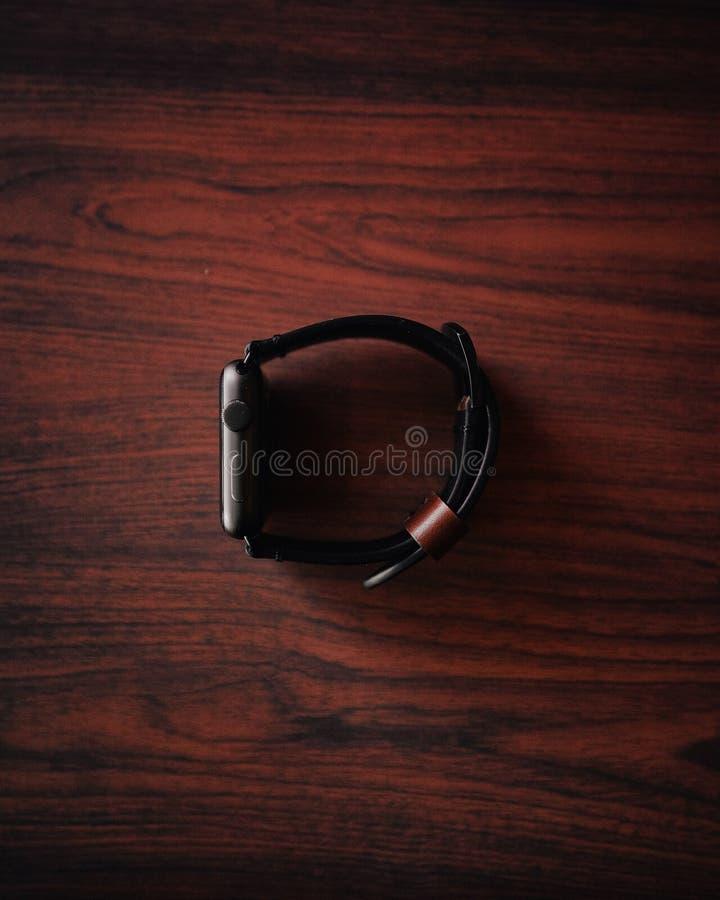 Closeup of a silver digital watch on a maroon wooden surface. A closeup of a silver digital watch on a maroon wooden surface royalty free stock photo