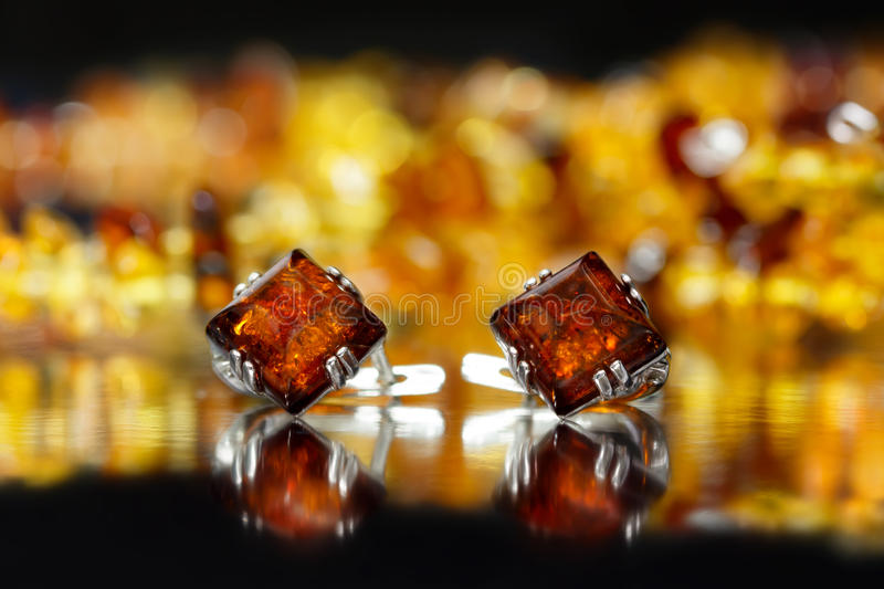 Closeup silver earrings rhombus with authentic natural baltic amber on black surface stock images