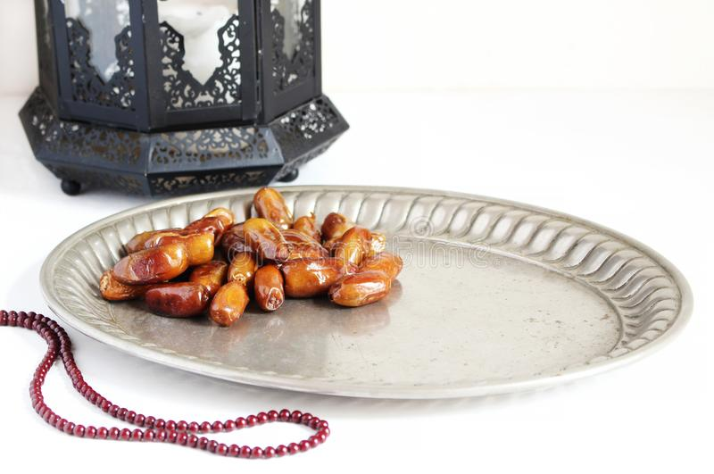 Closeup of silver plate with date fruits, prayer beads and ornamental dark Moroccan, Arabic lantern on the white table stock photos