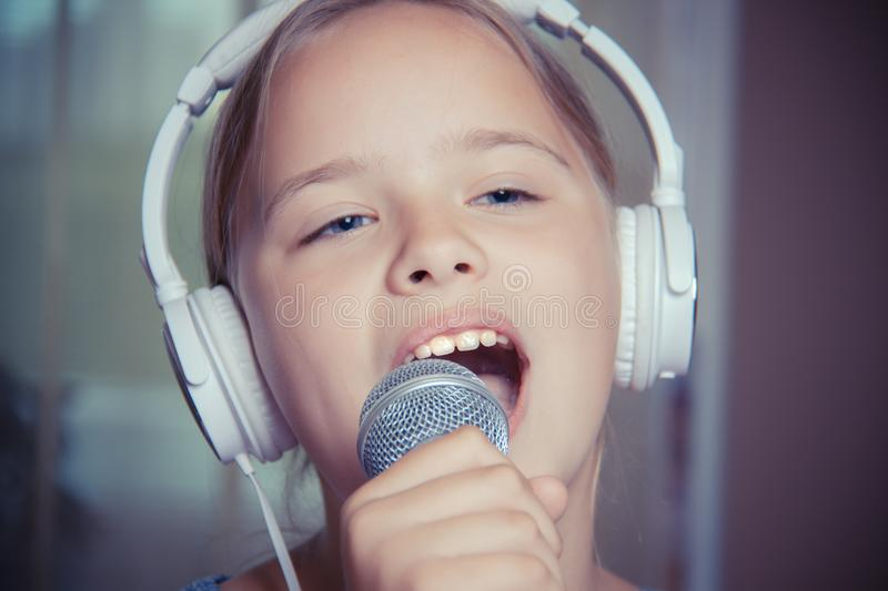 Closeup of singing caucasian child girl. Young girl emotionally sings into the microphone, holding it with hand. royalty free stock image