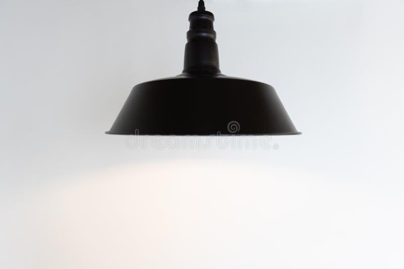 Closeup of single black hanging lamp on white wall background. Close up of single black hanging ceiling lamp on white wall background stock photos