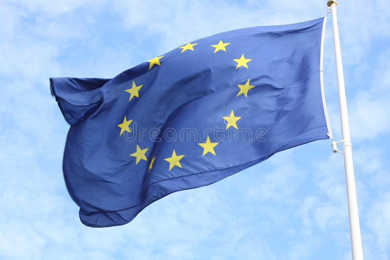 Closeup of single european flag with twelve yellow stars waving in the wind in front of blue sky royalty free stock photos