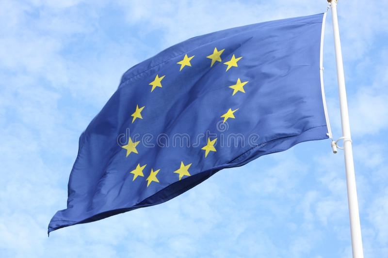 Closeup of single european flag with twelve yellow stars waving in the wind in front of blue sky royalty free stock photo