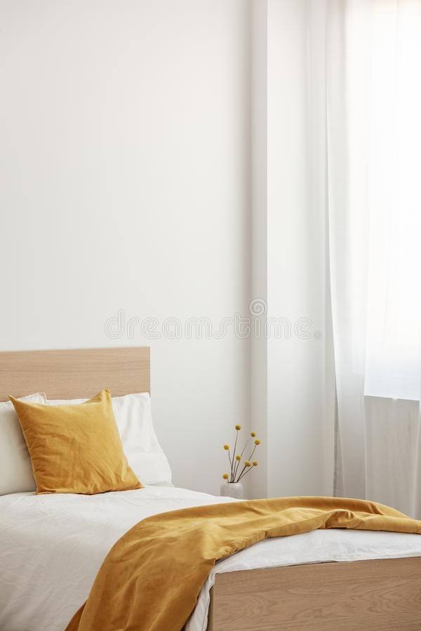 Closeup of single wooden bed with white and yellow bedding, copy space on empty wall stock photo