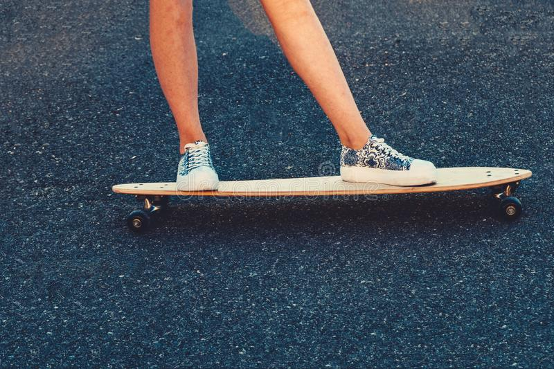 Closeup of skateboarder legs. Woman in sneakers riding skateboard outdoor. stock image