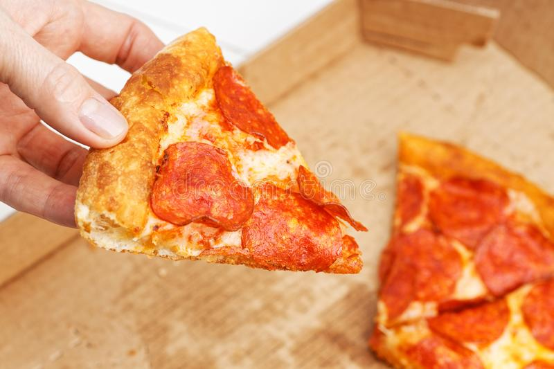 Closeup slice of italian pepperoni pizza in hand. And open box with pizza leftovers on blurred background royalty free stock images