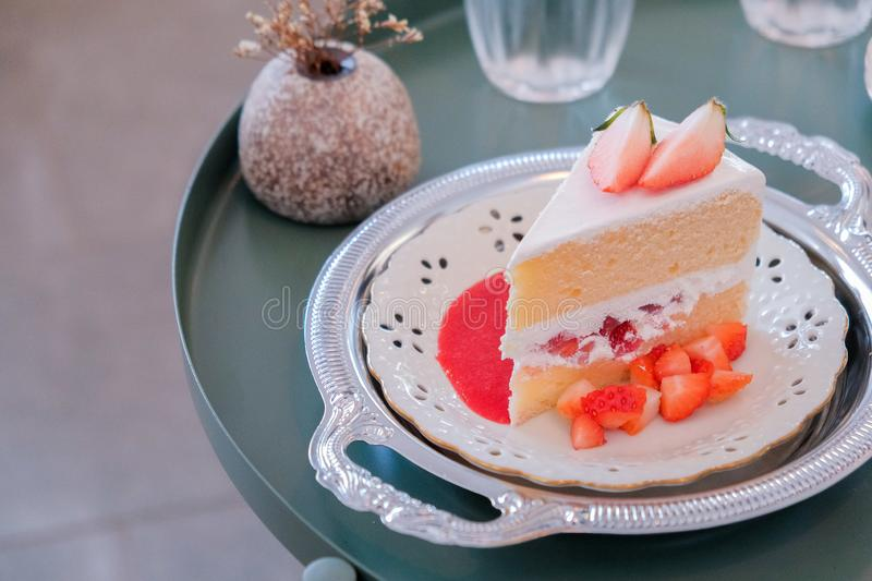A slice of sponge cake on the plate, Strawberry shortcake with sliced strawberries on wooden table. Closeup of a slice of sponge cake on the plate, Strawberry royalty free stock images