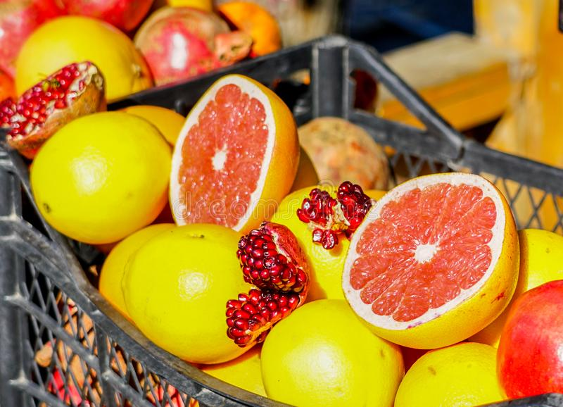 Closeup of sliced colorful fresh fruit, grapefruit and pomegranate at the streetmarket royalty free stock images