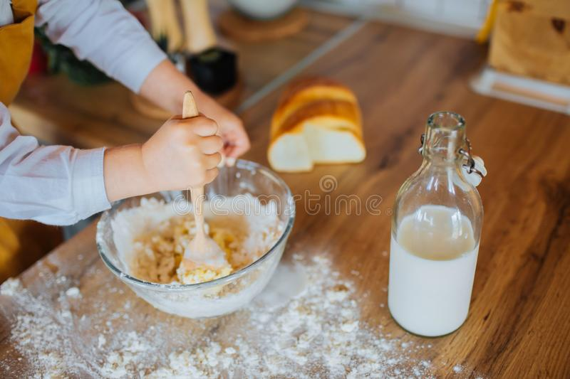 Closeup of small girl`s hands helping to bake. royalty free stock image