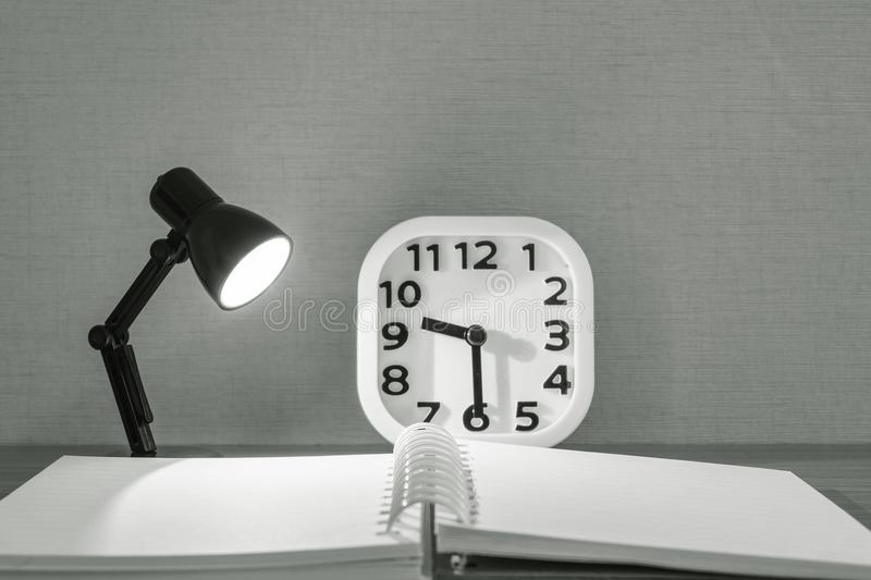 Closeup small lamp with light with blurred book and white alarm clock on wood desk textured background in black and white tone stock image