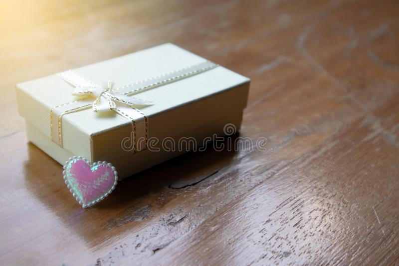 Closeup small white peatl gift box with white ribbon and the pink sparkle tiny heart royalty free stock images