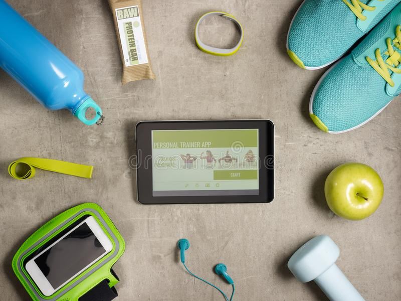 Closeup on smartphone and tablet PC with personal trainer app. Closeup on green apple, dumbbell, headphones, elastic band, raw protein bar, sneakers, fitness stock photos