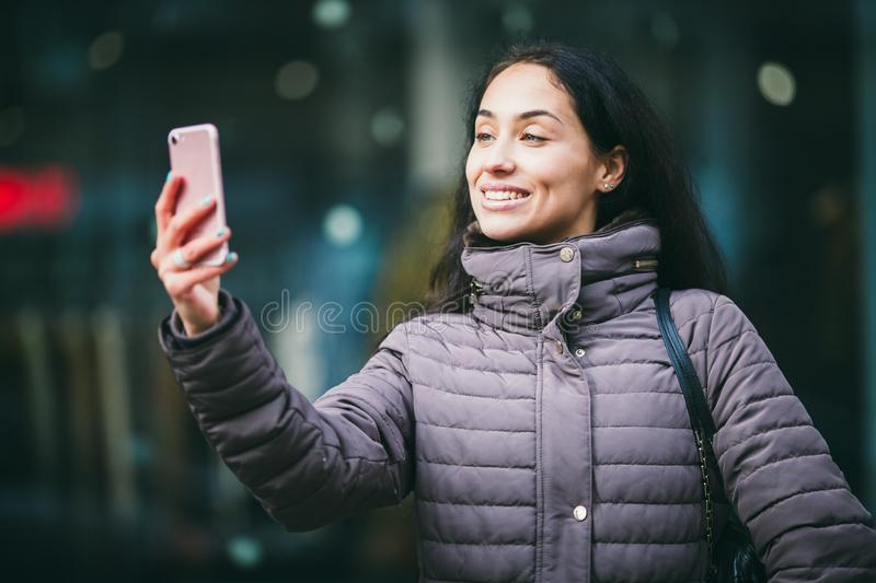 Closeup of smiling beautiful middle-aged business woman taking selfie on smartphone with blurred view in background stock image