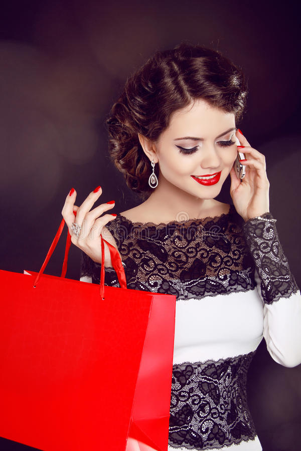 Closeup of a smiling beautiful young woman with shopping bag talking over the cellphone royalty free stock photo
