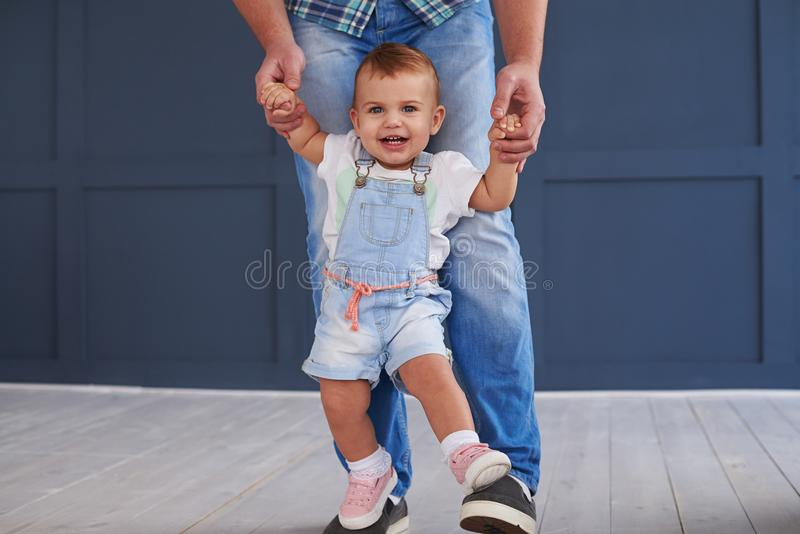 Smiling cute daughter doing her first steps with father stock photos