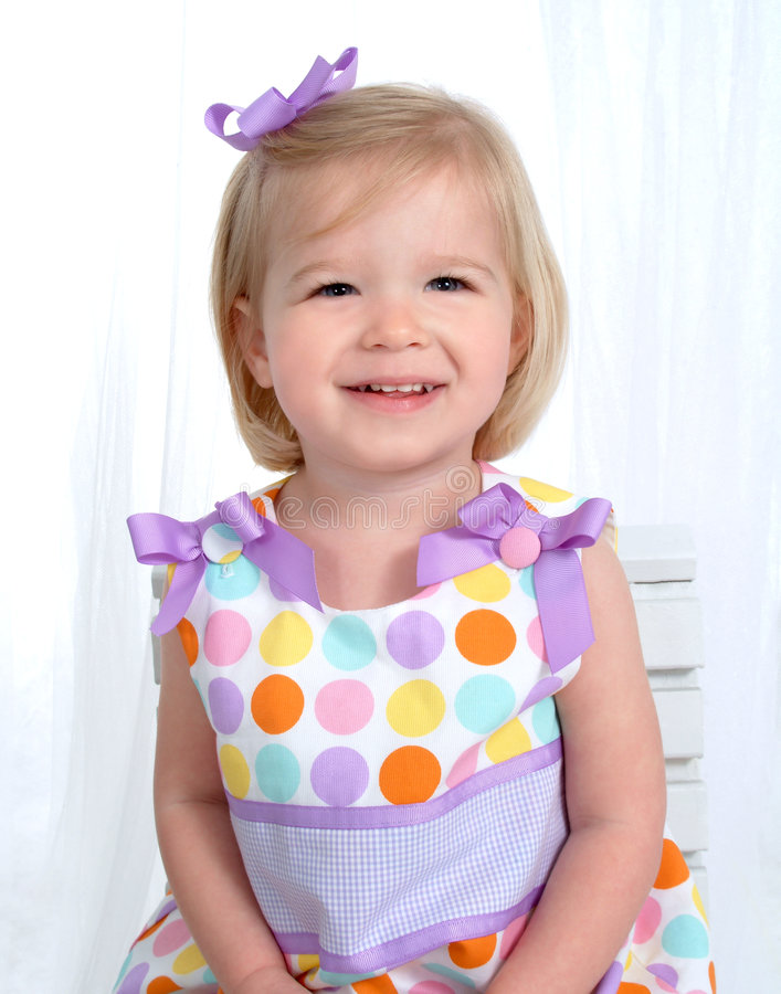 Closeup of Smiling Girl. Closeup of smiling blond girl in colorful polka dot dress in front of white background royalty free stock photo