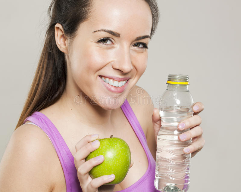 Closeup on smiling 20s athletic girl with symbols of health and nutrition for sporty lifestyle in hands royalty free stock photo