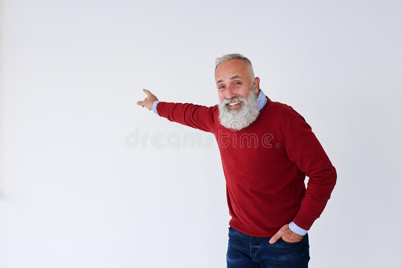 Smiling senior bearded man pointing backwards at copy space royalty free stock image