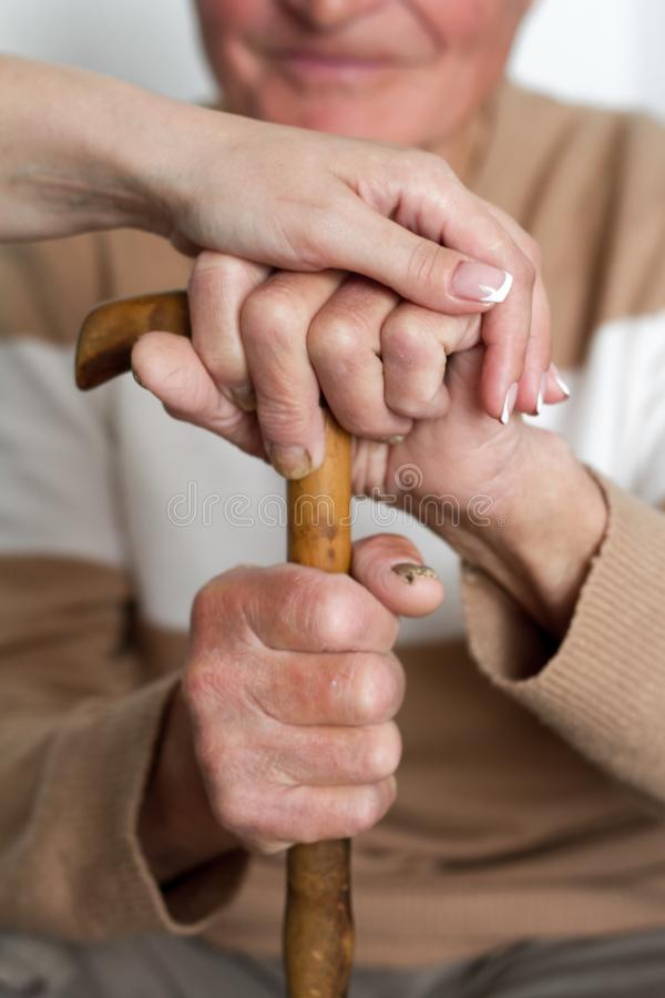 Closeup of smiling senior mans hands and young girl caregiver holding hands on walking stick royalty free stock images