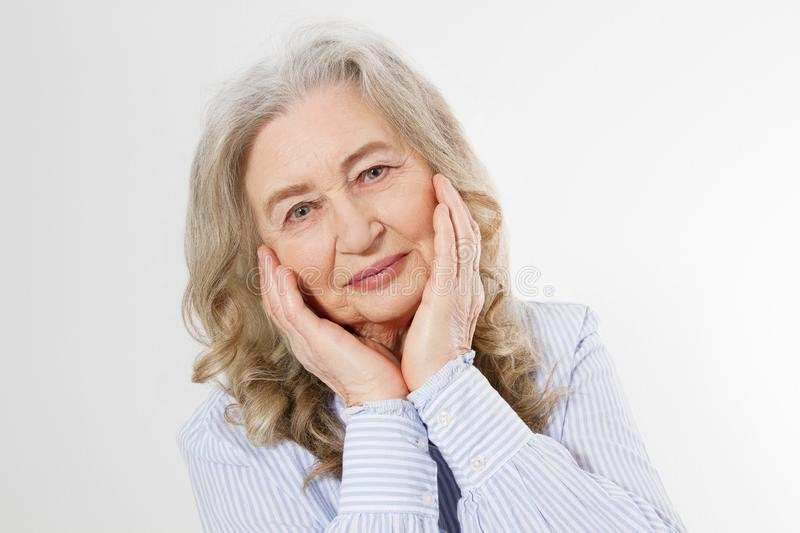 Closeup of smiling senior woman wrinkle face and gray hair. Old mature lady touching her wrinkled skin isolated on white stock image