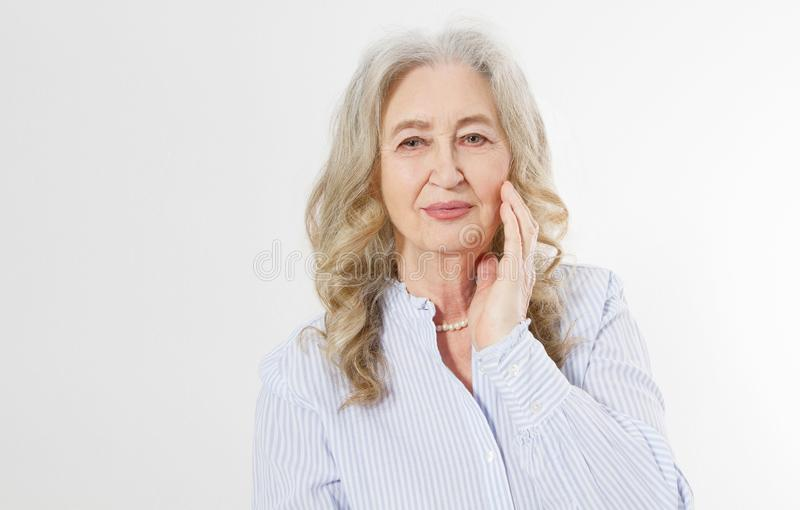 Closeup of smiling senior woman wrinkle face and gray hair. Old mature lady touching her wrinkled skin isolated on white stock images