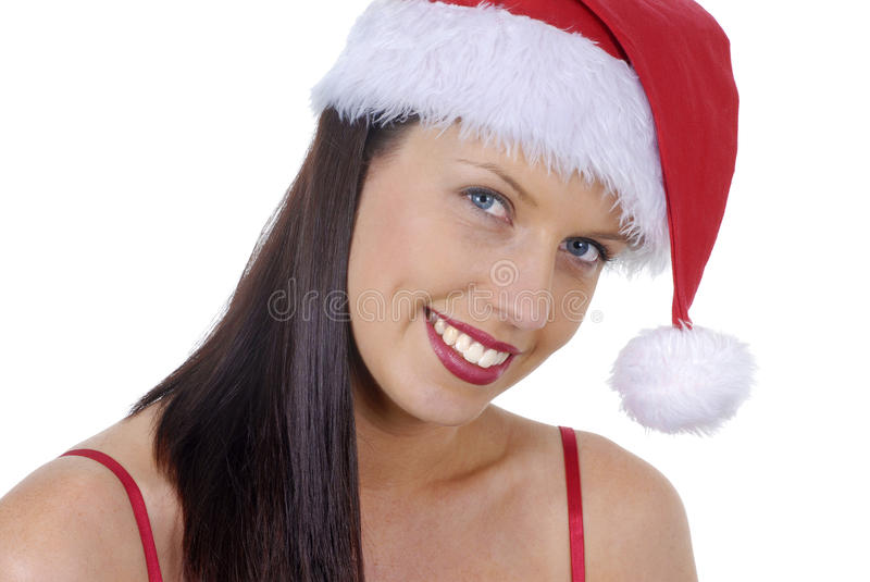 Closeup of smiling young adult woman with red Christmas Santa hat isolated on white stock image