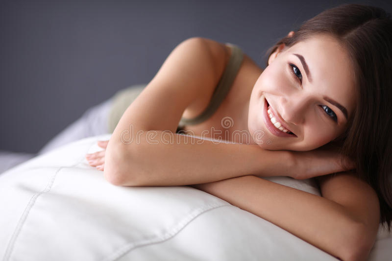 Closeup of a smiling young woman lying on couch royalty free stock images