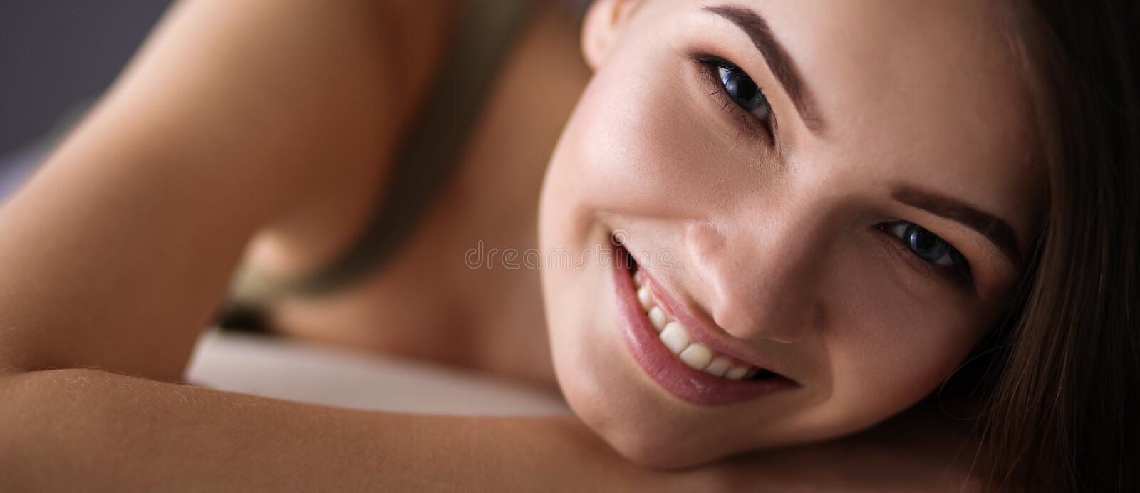 Closeup of a smiling young woman lying on couch stock images