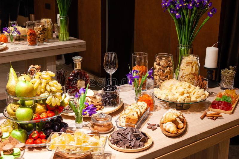 Closeup snacks, fresh and dried fruits, pieces parmesan cheese, honeycombs, dark chocolate, cinnamon sticks, nuts, biscotti. stock images