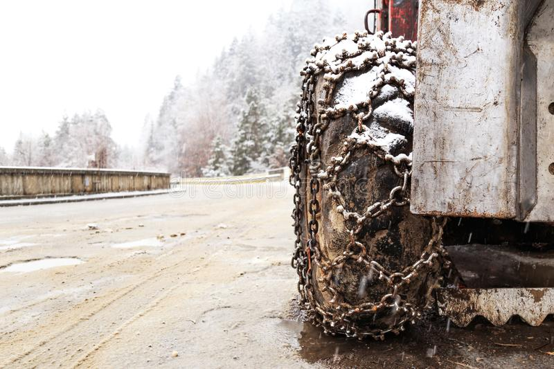 Closeup of snow chains mounted on a snowy car wheel. stock photos