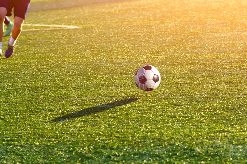 Closeup of a soccer ball in motion on a green football field. Sports background stock photo