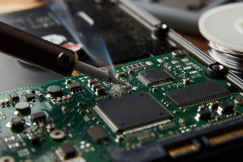 Closeup of Soldering of electronic circuit board. Electronic manufacturing and repair concept with soldering iron, wire and green microcircuit stock images