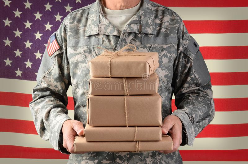 Soldier holding packages for Military Mail Call. Closeup of a soldier wearing camouflage fatigues holding a stack of packages for mail call. Horizontal format royalty free stock photos