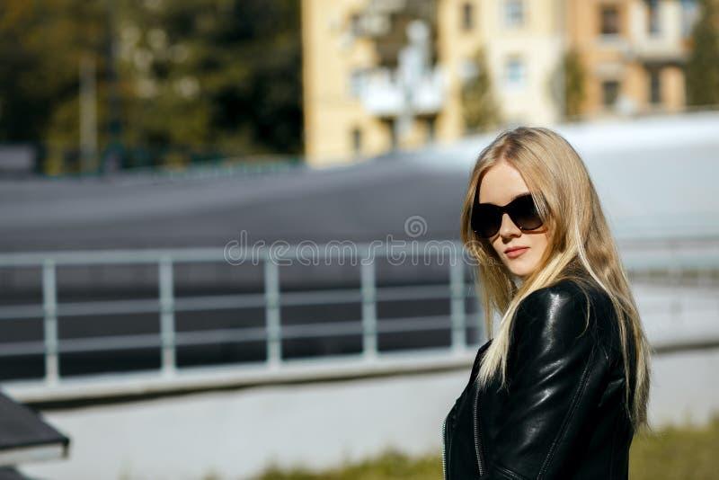 Closeup som skjutas av den nätta blonda modellen som bär det svarta läderomslaget och solglasögon Töm utrymme royaltyfria foton
