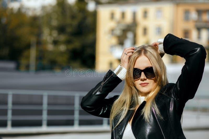 Closeup som skjutas av den trendiga blonda modellen som bär det svarta läderomslaget och solglasögon Töm utrymme royaltyfri foto