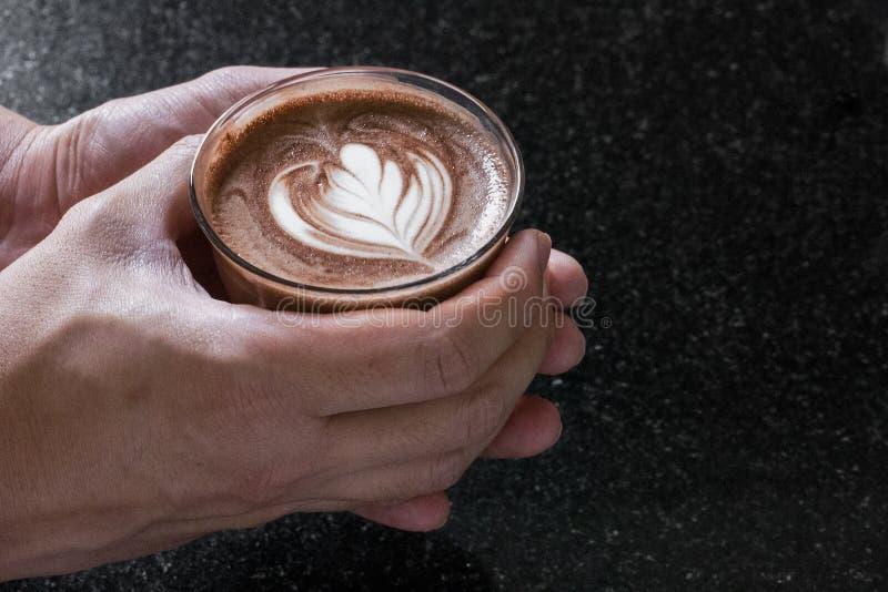 Closeup som skjutas av en persons händer som rymmer en varm kopp av cappuccino med härlig skumkonst på den royaltyfri foto