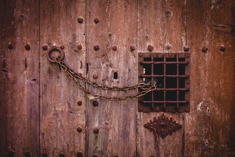 Closeup som skjutas av ett gammalt rostigt kedjelås på en stor trädörr med ett litet metallstaket arkivfoto
