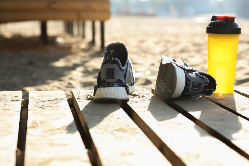 Closeup som skjutas av kvinnligt sportsko- och för vattenflaska anseende på stranden Töm utrymme arkivbild