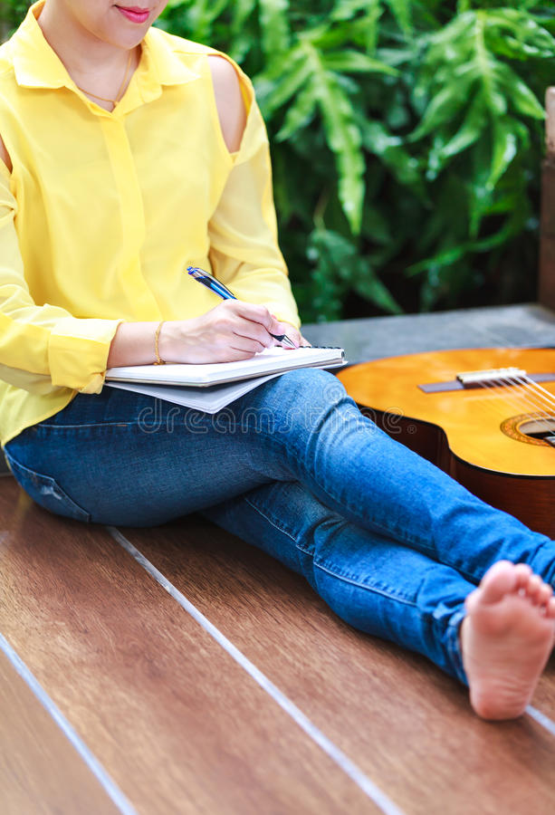 Closeup songwriter writing on note paper with acoustic guitar ne royalty free stock photos
