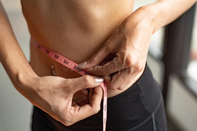 Closeup of sport happy slim woman using waist tape line in fitness gym sport club training center background. Success lifestyle o royalty free stock photo